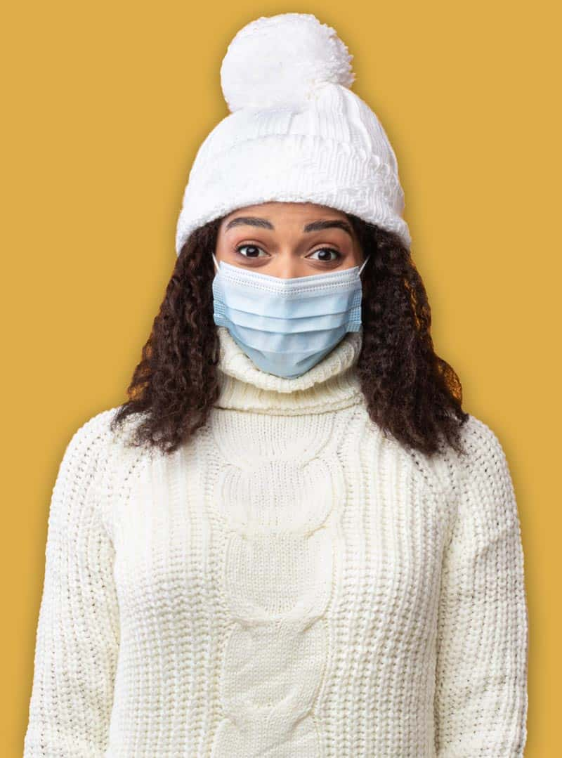 Photo of Black woman wearing a medical mask. She's dressed in a sweater and hat. There's a yellow background behind her.