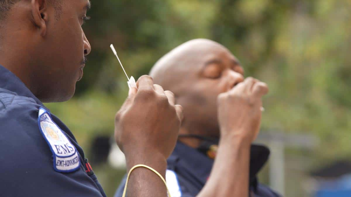 Photo of two Black EMS professionals administering self Covid-19 tests.