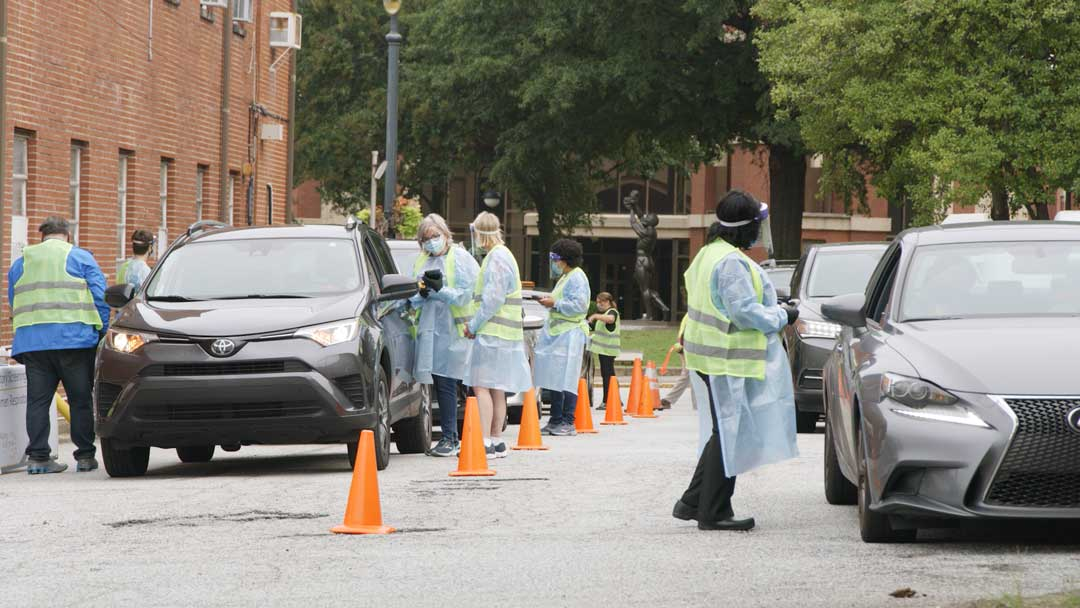 Photo of health professionals doing lung and Covid-19 screenings in a church parking lot