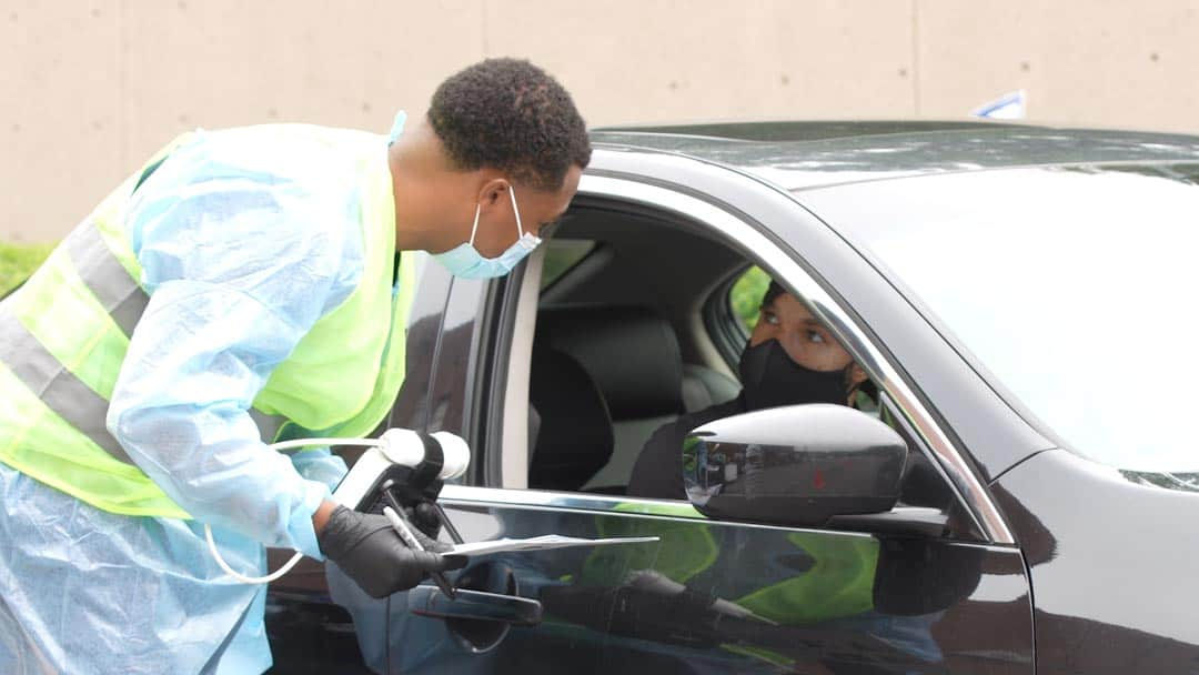 Health professional at Trusted Messengers pilot program in Atlanta. He's leaning over a car helping with lung screenings.